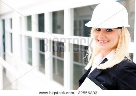 Young woman engineer wearing a safety hardhat inspecting work at the job site