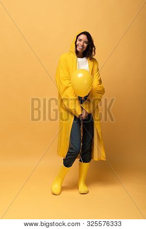 Smiling Curly Woman In Yellow Raincoat And Wellies Holding Balloon On Yellow Background