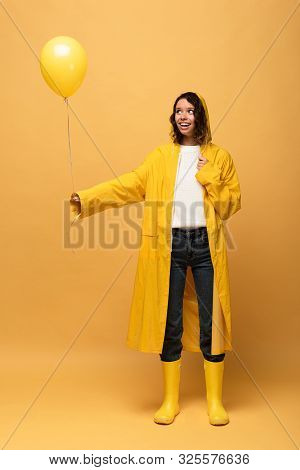 Happy Curly Woman In Yellow Raincoat And Wellies Holding Balloon On Yellow Background
