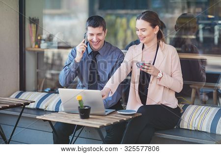 Elegant Two Young Business People Having An Informal Coffee Meeting - Happy Couple Sitting On A Cafe