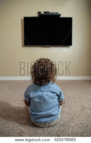 Rear view of a young child watching Television while sitting on the floor of his home. Selective focus on the back of the curly-haired diverse little boy.