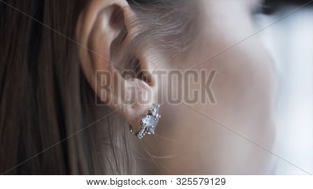Close Up Of Brunette Woman Hand Pushing Her Hair Back Behind Her Ear And Baring A Silver Earring. Ac