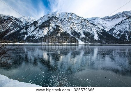 Bavarian Winter Landscape. Beautiful Panoramic View Of Frozen Lake And Mountains. Alps Mountain Refl