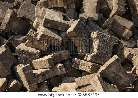Sun shines on old discarded (segmental paver) paving stones poster