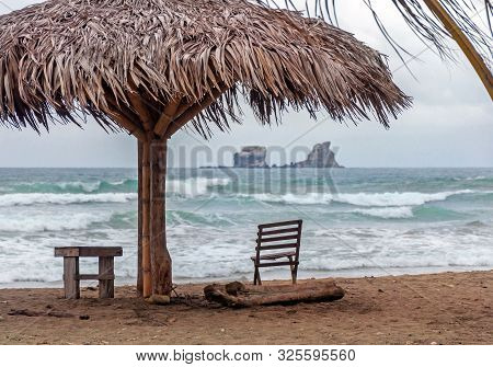 Beach Parasol With A Chair And Bench In Front Of The Ocean, On An Overcast Morning. Ayampe, Manabi,