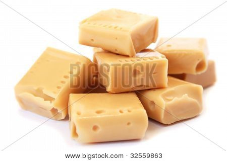 Pile of caramel candies isolated on white background. poster
