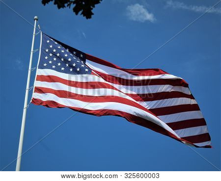 An American Flag Flaps In A Warm Breeze On A Sunny September Day.