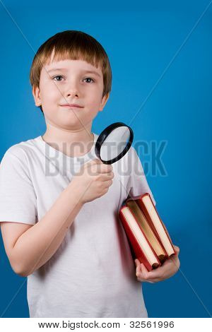 Boy With Magnifying Glassa And Pile Of Books