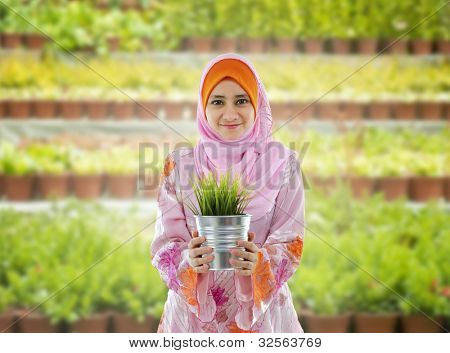 Concept of young Muslim girl holding a plant on nursery