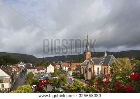Townscape with rain clouds of Niederbronn les Bains in France poster