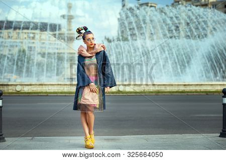 Avant garde style with funky street fashion model woman with crazy hair posing on city street poster
