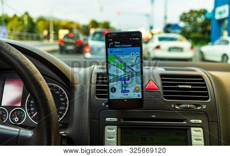 In Car Dashboard View With Smartphone Showing Waze Maps To Show The Way Thru The City In Bucharest,