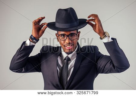 Retro Style Well Dressed African American Business Man Model In Dark Suit And Black Hat In Studio On
