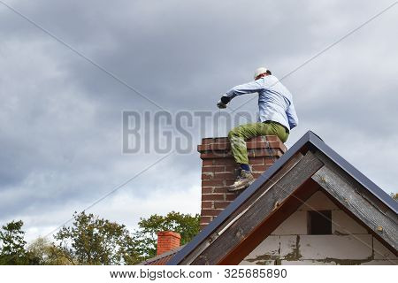 Chimney Sweep Man Cleaning Brown Brick Chimney While Sitting On Chimney On Building Roof On Cloudy S