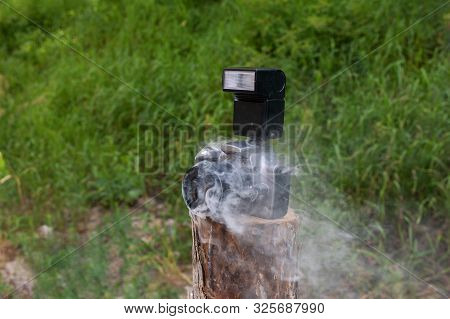 Smoldering Digital Camera With Zoom Lens. Technical Malfunction, Problem With Electronics, Violation