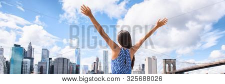 NYC New York city happy freedom woman cheering arms up raised in the sky. Success in business career, goal achievement or carefree freedom successful urban person concept. Banner landscape.