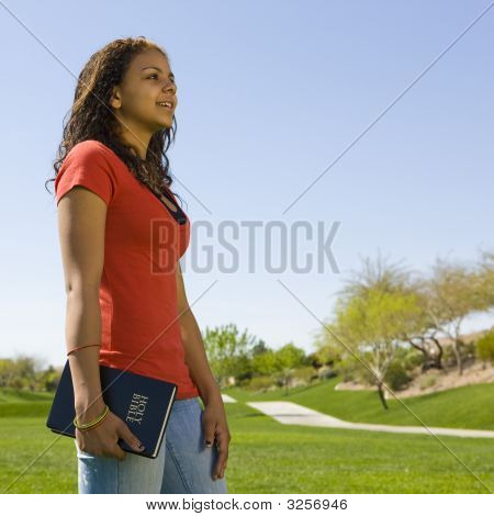 Teen With Bible In Park