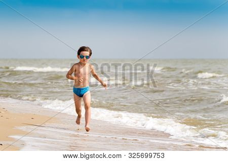 A Boy In Sunglasses Runs Along The Sea Coast On Golden Sand. Rest Of Children On Summer Vacation. Ho