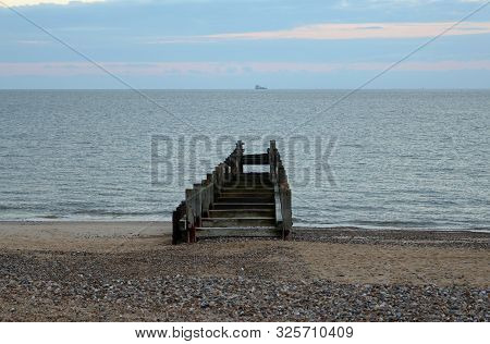 Wooden Breakwater Pointing To Ship On Horizon With Sand And Pebble Beach In Foreground. Sea With Sun