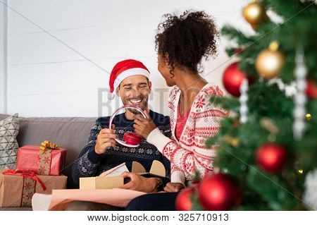 Happy man receiving red wireless headphone as christmas present. Multiethnic couple unwrapping xmas present on sofa. Husband wearing santa claus hat and wife opening xmas present with earphone in it.