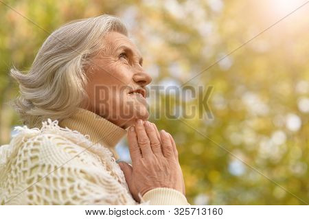 Portrait Of A Happy Senior Woman Smiling Praying