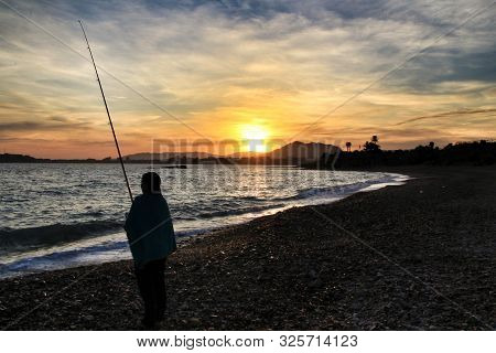 Fisherman at Sunset on Mojon beach in Isla Plana, Cartagena, Murcia,Spain. poster