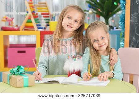 Portrait Of Cute Sisters Drawing With Pencils