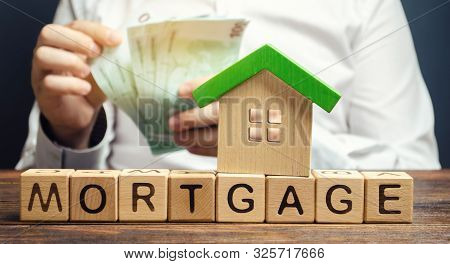 Wooden Blocks With The Word Mortgage And Money In The Hands Of A Businessman. The Concept Of Buying