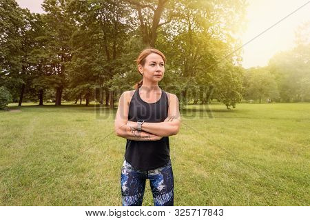 Beautiful And Athletic Girl With Clothes For Jogging Standing With Her Hands Crossed Over Her Chest