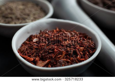 Spice Red Paprika In A White Ceramic Bowl Next To A Pounder On A Black Background