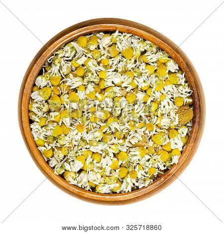 Dried Chamomile Blossoms In Wooden Bowl. Camomile Tea, Flowers Of Matricaria Chamomilla, Used For He