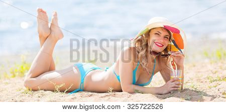 Pretty Woman 30-35 Years Old In Blue Bikini Sunbathes On The Beach Holds Juice In Her Hand