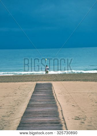 Wooden Walkway And Woman Walking Along The Beach Of Gandia, Valencia, On A Rainy And Cloudy Day