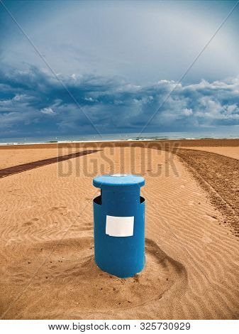Close-up Of A Blue Wastebasket On The Beach Of Gandia, Valencia, On A Day With The Sky Covered With