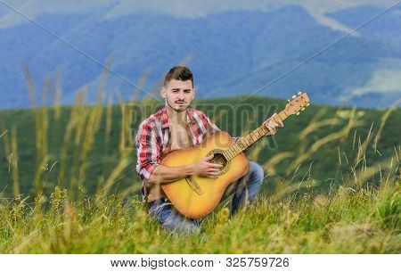 Inspiring environment. Man with guitar on top of mountain. Acoustic music. Summer music festival outdoors. Playing music. Sound of freedom. Inspired musician play rock ballad. Compose melody poster