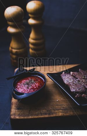 Beef steak cut into strips on a cutting board with tomato sauce next to it and with kitchen utensils. poster
