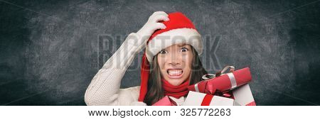 Christmas stress holiday shopping woman in santa hat stressed funny expression on black blackboard banner panorama. Anxious lady shopper late for christmas gifts stressing about the budget spending.