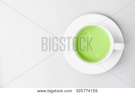 Top view of green tea matcha in a white mug. Matcha ginger latte. Rich source of antioxidants and polyphenols. Copy space for text poster