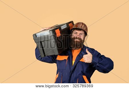 Builder Man Carrying Tool Box Giving Thumbs Up. Repairman In Overall Hold Toolbox. Man With Tool Box