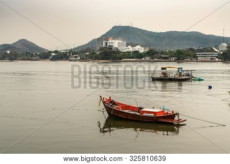 Si Racha, Thailand - March 16, 2019: Couple Of Small Fishing Vessels On Flat Gray Water Just Off Bea