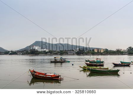 Si Racha, Thailand - March 16, 2019: Multiple Small Fishing Vessels On Flat Gray Water Just Off Beac