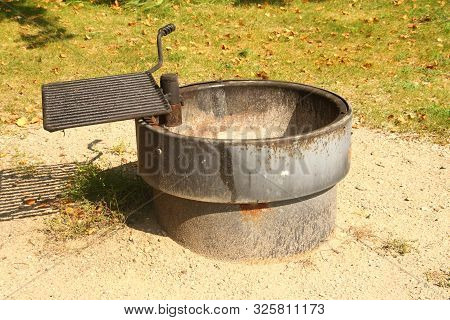 A Cast Iron Firepit With A Cooking Grate Located In A State Park In Minnesota.