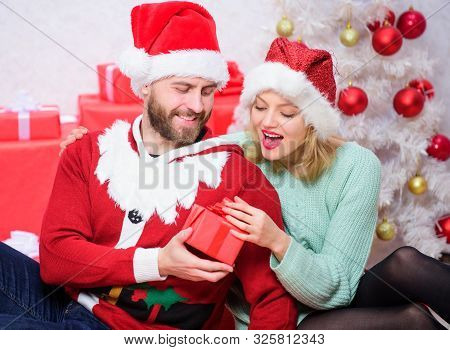 Gift to beloved. Family prepared christmas gifts. Loving couple cuddle smiling while unpacking gift christmas tree background. Couple in love happy enjoy christmas holiday celebration with gifts poster