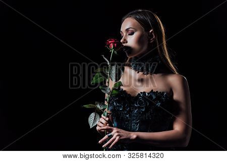 Scary Vampire Girl In Black Gothic Dress Holding Red Rose Isolated On Black