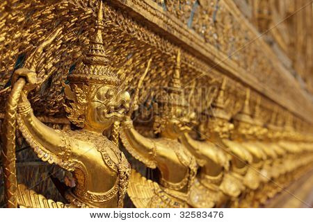perspective view of golden religious statue in wat phra kaeo temple, Bangkok, Thailand, shallow depth of field