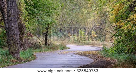 windy bike trail along the Poudre River in Fort Collins, Colorado - rainy day with fall colors, panoramic format