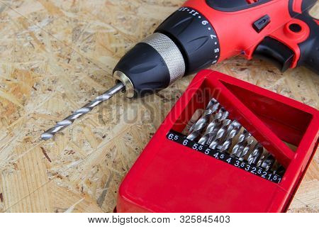 Electric Screwdriver With Drill Set, Red Electric Drill With Drill And Drill Set On Wooden Backgroun