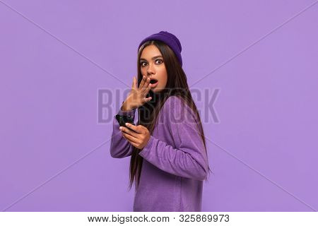 Pretty African-american Girl In A Hat And Sweater Holding Smartphone And Expressing Emotion Of Surpr
