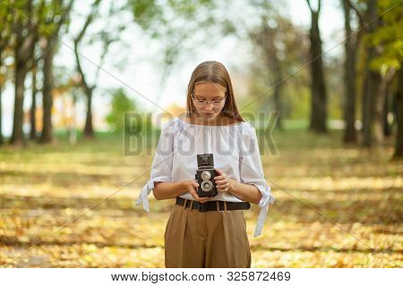 Attractive Beautiful Young Girl Holding Retro Vintage Twin Lens Reflection Camera In Autumn Park. Ye