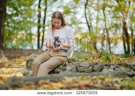 Attractive Beautiful Young Girl Holding Retro Vintage Twin Lens Reflection Camera In Autumn Park.